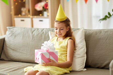 Happy girl in party hat with birthday gift at home