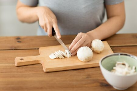 Woman cutting champignons by knife on board