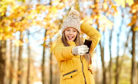 Girl taking selfie by smartphone at autumn park