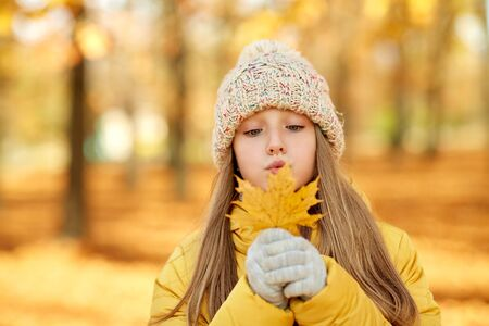 Portrait of girl with maple leaf at autumn park