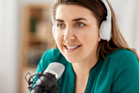 Woman with microphone recording podcast at studio