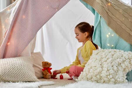 Girl playing tea party with teddy in kids tent Фото со стока