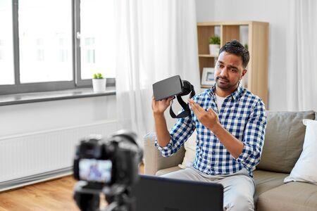 Male blogger with vr glasses video blogging at home Banco de Imagens