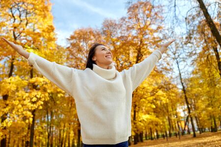 Beautiful happy young woman in autumn park