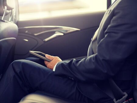 transport, business trip, technology and people concept - senior businessman with tablet pc computer driving on car back seat Stock Photo