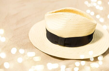 summer holidays and vacation concept - straw hat on beach sand