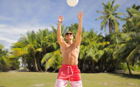 summer holidays, sport, fitness and people concept - young man with ball playing volleyball over tropical beach background in french polynesia Фото со стока