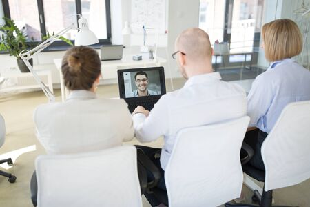 business, employment and technology concept - team of employers having video conference or job interview with new employee at office