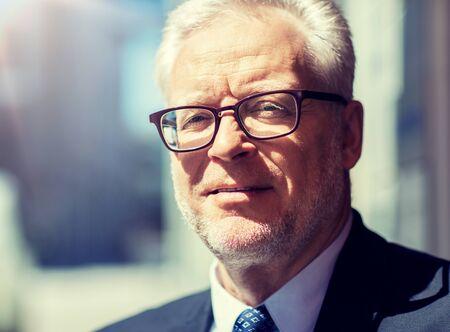 koncepcja biznesu i ludzi - zbliżenie starszego biznesmena w okularach i garniturze