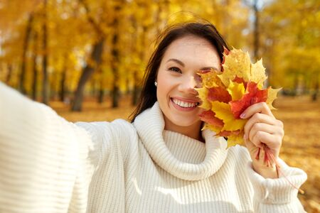 woman with leaves taking selfie in autumn park