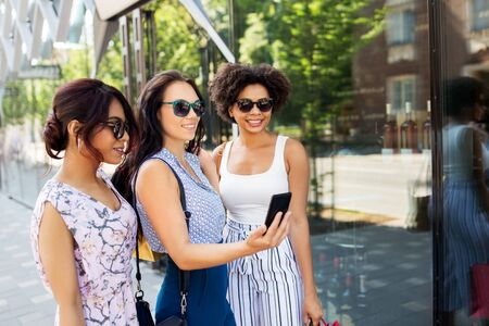 sale, friendship and technology concept - happy young women with shopping bags taking selfie by smartphone in summer city