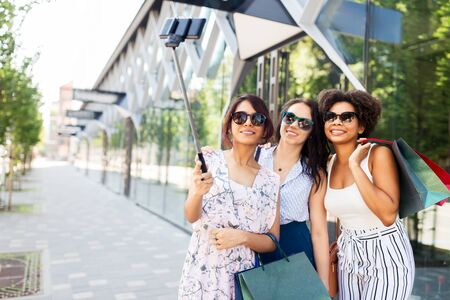 women with shopping bags taking selfie outdoors Stock Photo