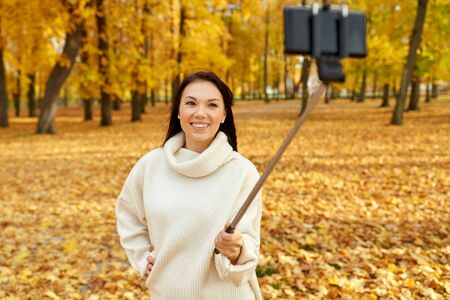 woman taking selfie by smartphone at autumn park