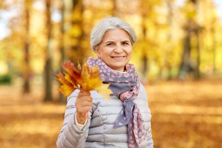 old age, retirement and season concept - portrait of happy senior woman with maple leaves at autumn park