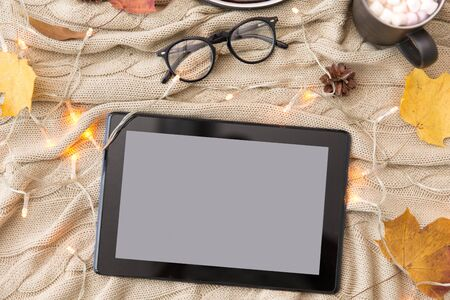 technology and season concept - tablet computer, autumn leaves, hot chocolate and glasses with garland lights on warm knitted blanket Banco de Imagens