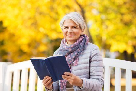 Alters-, Ruhestands- und Menschenkonzept - glückliche ältere Frau, die auf der Bank sitzt und ein Buch im Herbstpark liest Standard-Bild