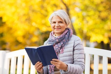 old age, retirement and people concept - happy senior woman sitting on bench and reading book at autumn park Stock fotó