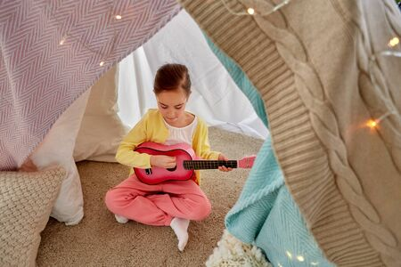 childhood and hygge concept - little girl playing guitar in kids tent or teepee at home