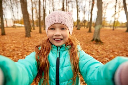 season and people concept - happy girl taking selfie at autumn park