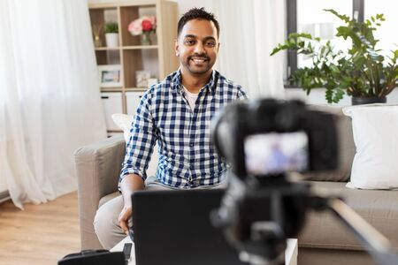 blogging, videoblog and people concept - indian male blogger with camera recording video at home Banco de Imagens