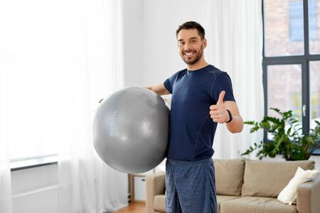 fitness, sport and healthy lifestyle concept - man exercising with ball at home Stock Photo - 125269676