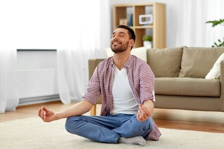 mindfulness, meditation and relaxation concept - man meditating in lotus pose at home