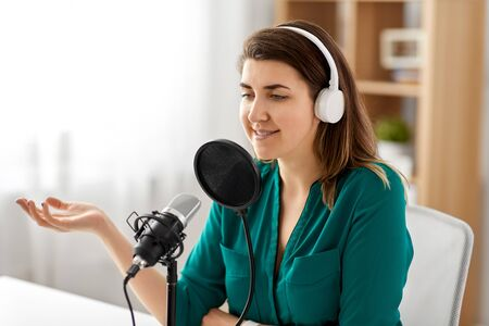 technology, mass media and people concept - woman with microphone and headphones talking and recording podcast at studio