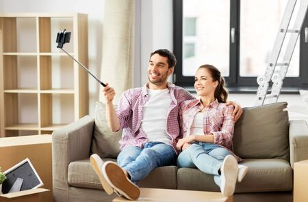 moving, repair and real estate concept - smiling couple taking picture by selfie stick at new home
