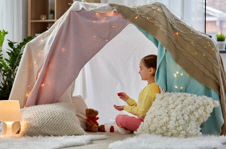 childhood and hygge concept - happy little girl playing tea party with teddy bear in kids tent at home Banco de Imagens