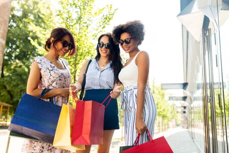 sale, consumerism and people concept - happy young women showing shopping bags on city street