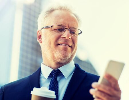 businessman with smartphone and coffee in city