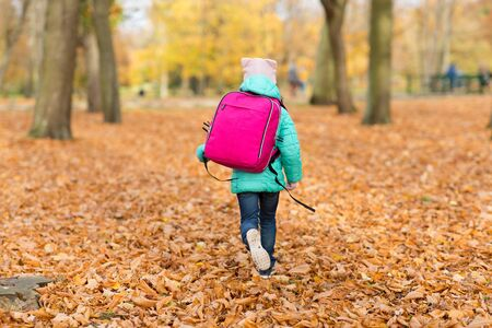 education and season concept - elementary student girl with school bag at autumn park