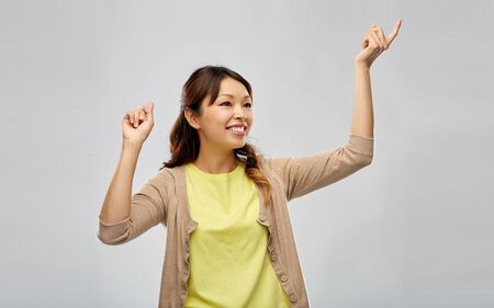 people and leisure concept - happy young asian woman dancing over grey background