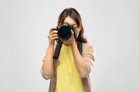 photography, profession and people and concept - asian female photographer with digital camera