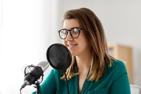 woman with microphone recording podcast at studio Stockfoto