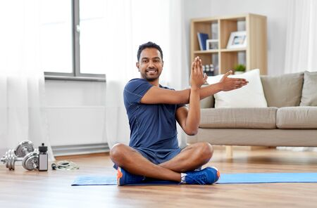 sport, fitness and healthy lifestyle concept - indian man training and stretching arm at home