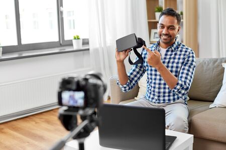 blogging, videoblog and people concept - indian male blogger with camera recording video review of vr glasses at home Stock Photo