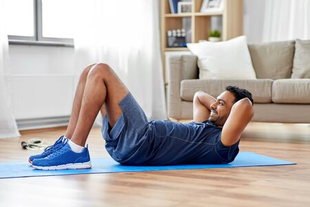 sport, fitness and healthy lifestyle concept - indian man making abdominal exercises at home Archivio Fotografico