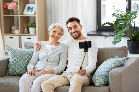 family, generation and people concept - happy smiling senior mother with adult son taking picture by selfie stick at home