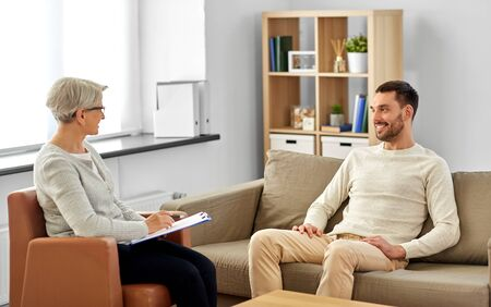 psychology, mental therapy and people concept - smiling senior woman psychologist with clipboard talking to young man patient at psychotherapy session