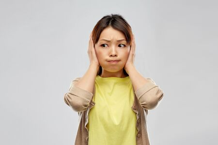 asian woman closing ears by hands Imagens