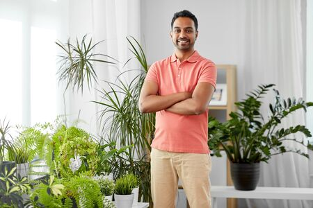 smiling indian man with houseplants at home Standard-Bild