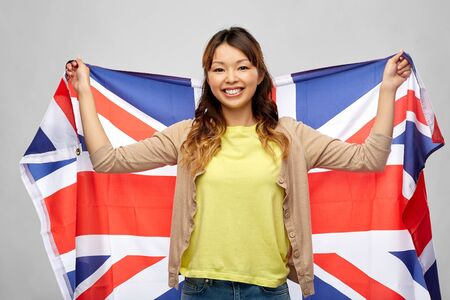 happy asian woman with british flag over grey