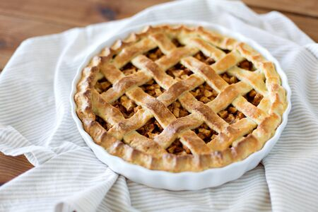 Close up of apple pie in mold on wooden table Foto de archivo