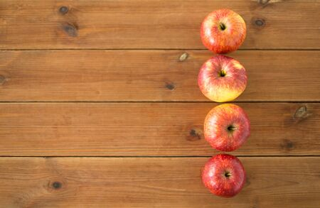 Ripe red apples on wooden table
