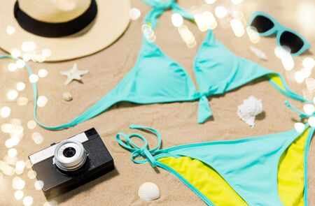 Vacation, travel and summer concept - bikini, hat, camera and sunglasses with seashells s on beach sand