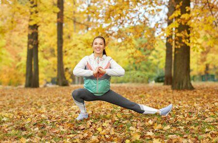 Jeune femme faisant du sport au parc d'automne Banque d'images