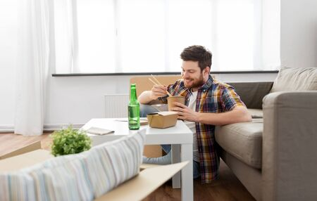 Moving, consumption and people concept - smiling man eating takeaway food for lunch at new home
