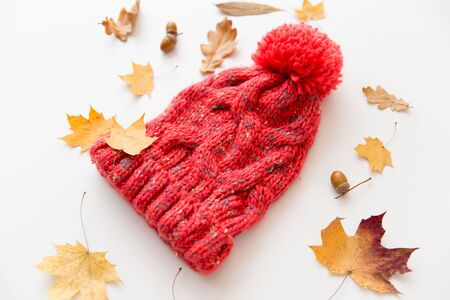 Season, headwear and clothes concept - knitted woolen hat and fallen autumn leaves on white background Archivio Fotografico - 125731472