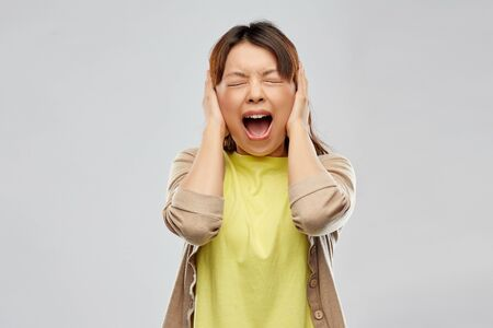People, emotion and stress concept - Asian young woman closing ears by hands and screaming over grey background